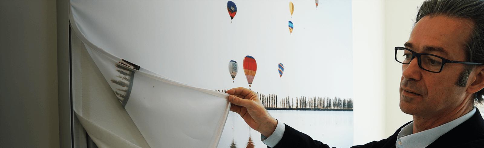 Pieter Niessen von objectiv in Köln schaut sich eine Leinwand zur Akustikverbesserung an