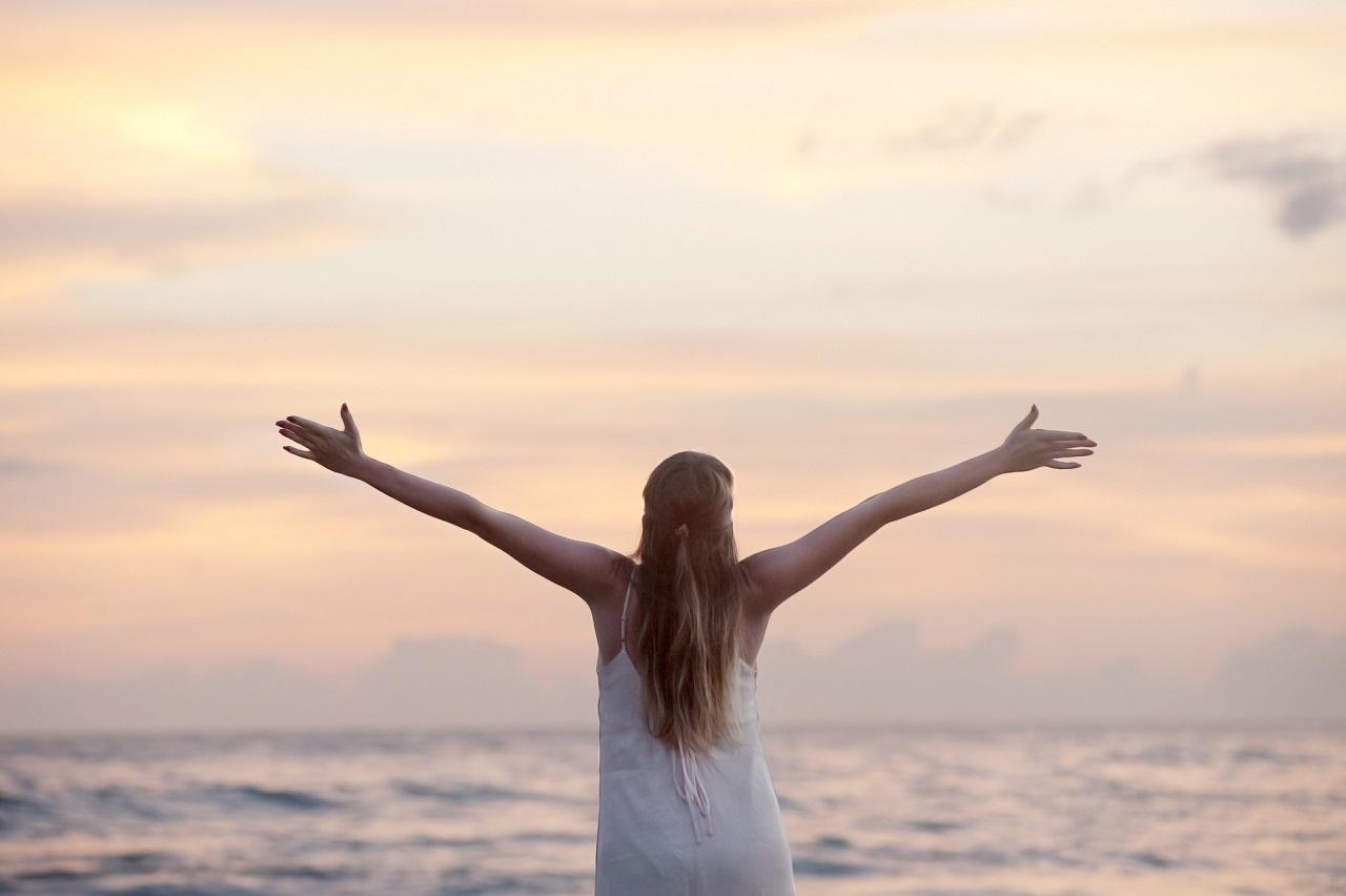 7 Gründe, warum mich ehrenamtliches Engagement so glücklich macht. Zu sehen: Eine Frau vor dem Horizont, die die Arme weit ausstreckt.