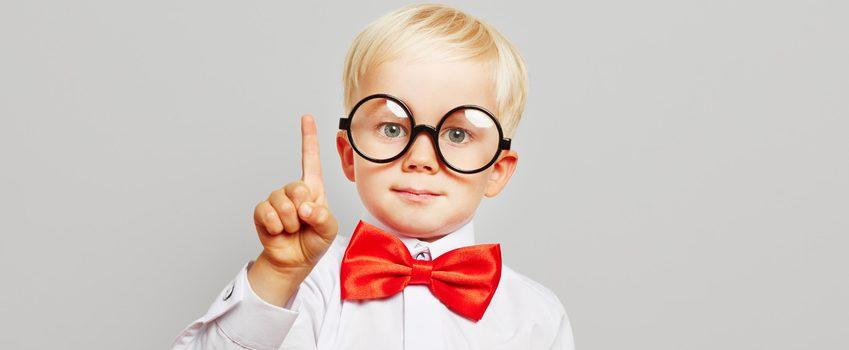 Kind mit Brille, roter Fliege und weißem Hemd hebt den Finger und hat eine Idee