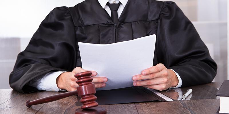Ein Richter hält ein Dokument in der Hand.