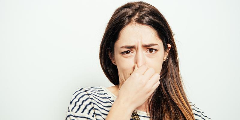 Eine Frau hält sich die Nase zu.