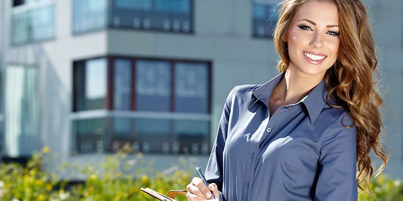 Immobilienverwalterin posiert mit einem Stift in der Hand vor einer Immobilie